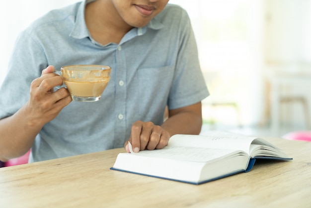 Zamyka w górę młodego człowieka czyta książkę dla wzrostowej wiedzy edukaci podczas ma kawę w kawiarni