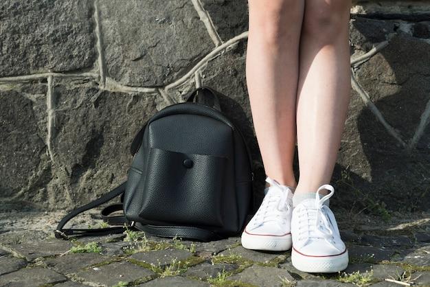 Zamyka w górę nastoletniej dziewczyny z plecakiem na ziemi