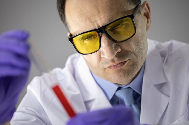 Zamyka w górę naukowca analizuje ciecz w próbnej tubce w żółtych ochronnych szkłach