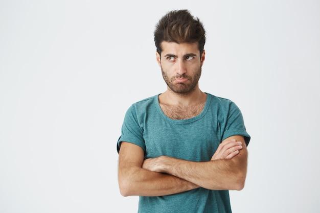 Zamyka w górę odosobnionego portreta nieszczęśliwy latynoski facet w modnych ubraniach i ostrzyżeniu, patrzejący daleko od, ściskający wargi wyrażający zniewagę i niezadowolenie. ludzkie emocje. skopiuj miejsce