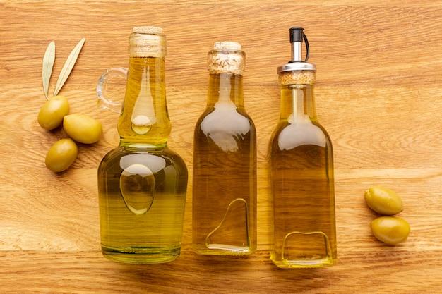 Zamyka w górę oliwnych butelek żółtych oliwek i liści