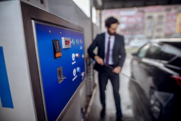 Zamyka w górę ostrość widoku monety maszyna podczas gdy elegancki brodaty młody pracowity mężczyzna myje jego czarnego samochód z pistoletem wodnym na ręcznej samoobsługowej myjni samochodowej w kostiumu.