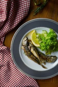 Zamyka w górę piec na grillu szprotowej ryba z sałatką na bielu talerzu w składzie z czerwonym płótnem na drewnianym stole.