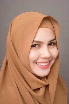 Zamyka w górę pięknej kobiety z hijab na szarym tle