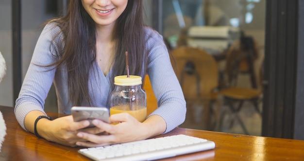 Zamyka w górę pięknej młodej azjatykciej kobiety w kawiarni, używać telefon komórkowego i pić kawę