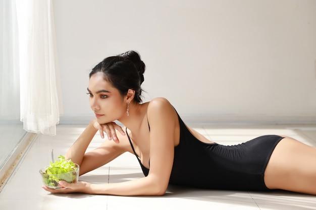 Zamyka w górę pięknej zdrowej i sporty azjatykciej młodej kobiety trzyma sałatkowego puchar i je po trenować
