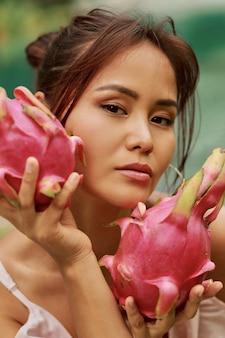 Zamyka w górę piękno portreta ładna azjatycka kobieta z smok owoc obok twarzy.