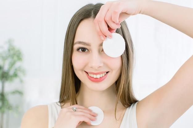 Zamyka w górę piękno portreta uśmiechnięta atrakcyjna kobieta czyści jej twarz z bawełnianym ochraniaczem odizolowywającym nad lekkim tłem. koncepcja pielęgnacji i urody skóry