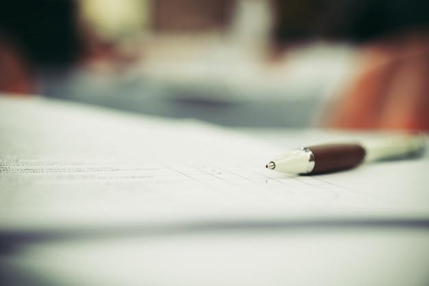 Zamyka w górę piór na formularzowej papierkowej robocie przy sala konferencyjnej lub seminarium spotkaniem, biznesowy edukaci pojęcie