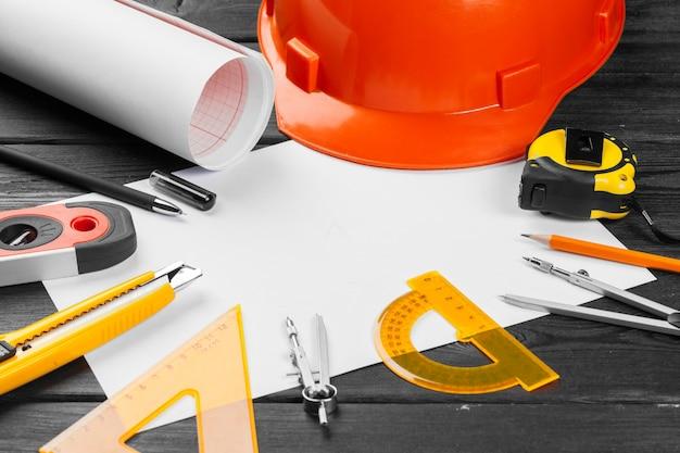 Zamyka w górę pomarańczowego hardhat i rozmaitości remontowi narzędzia z copyspace w środku nad drewnianym