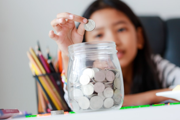 Zamyka w górę portret małej azjatyckiej dziewczyny kładzenia pieniądze monety w szklaną słoju prosiątka banka wybiórki ostrości płytką głębię pole