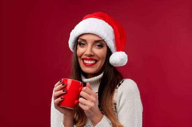 Zamyka w górę portret pięknej caucasian kobiety w czerwonym santa kapeluszu na czerwieni ścianie. koncepcja nowego roku bożego narodzenia. śliczni kobieta zęby uśmiecha się pozytywne emocje z czerwoną filiżanką kawy w rękach