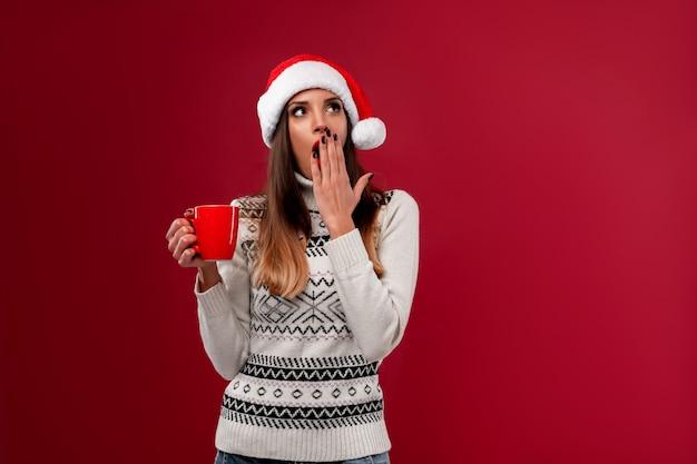 Zamyka w górę portret pięknej caucasian kobiety w czerwonym santa kapeluszu na czerwieni ścianie. koncepcja nowego roku bożego narodzenia. zęby kobiety uśmiechnięte pozytywne emocje z czerwoną filiżanką kawy leniwy śpioch