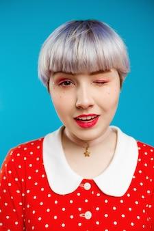 Zamyka w górę portret pięknej lalkowatej dziewczyny z krótkim jasnofioletowym włosy jest ubranym czerwonej suknię mruga nad błękit ścianą
