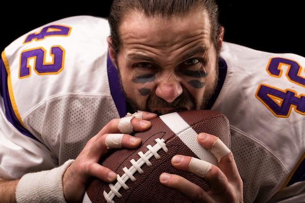 Zamyka w górę portreta agresywny futbolu amerykańskiego gracz agresywny gracz gryźć jego piłkę