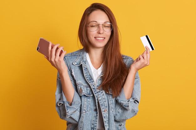 Zamyka W Górę Portreta Atrakcyjny Kobiety Areszt Przy Sądzie Telefon I Kredytowa Karta W Rękach Premium Zdjęcia