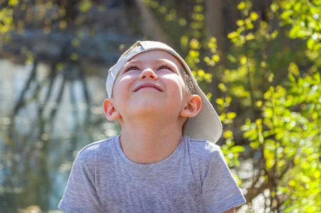 Zamyka w górę portreta chłopiec z uśmiech twarzą patrzeje zamyślenie przy niebem w lato słonecznym dniu. radosny letni nastrój. dzień ochrony dzieci. selektywne ustawianie ostrości, sztuczny hałas