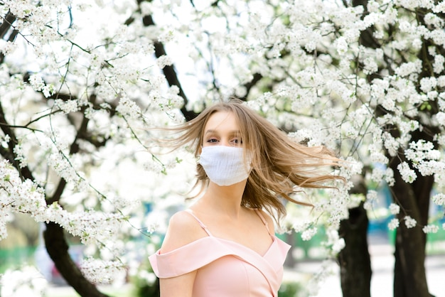 Zamyka w górę portreta czuła dziewczyna w białej bluzce pod kwitnącym czereśniowym drzewem z maską od koronawirusa.