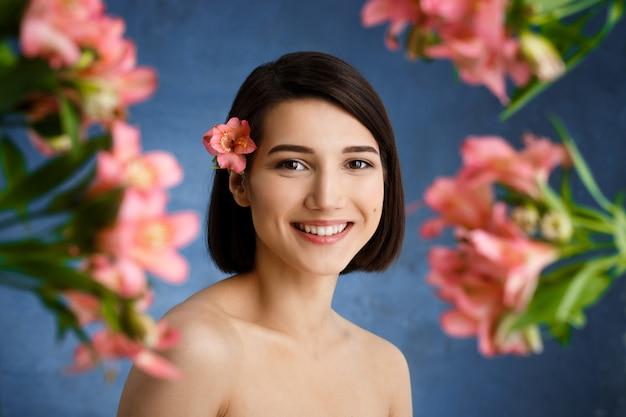 Zamyka w górę portreta czuła młoda kobieta z blured różowymi kwiatami nad błękit ścianą
