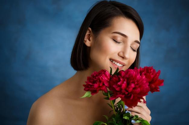 Zamyka w górę portreta czuła młoda kobieta z czerwonymi kwiatami nad błękit ścianą
