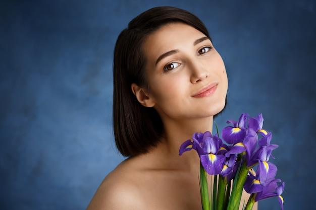 Zamyka w górę portreta czuła młoda kobieta z fiołkowymi irysami nad błękit ścianą