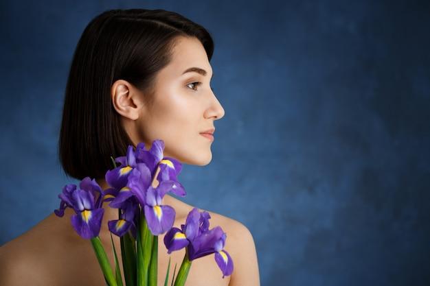 Zamyka w górę portreta czuła młoda kobieta z fiołkowymi kwiatami nad błękit ścianą