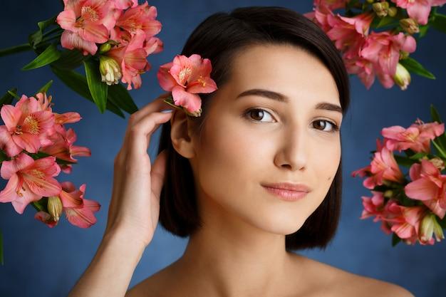 Zamyka w górę portreta czuła młoda kobieta z kwiatami nad błękit ścianą