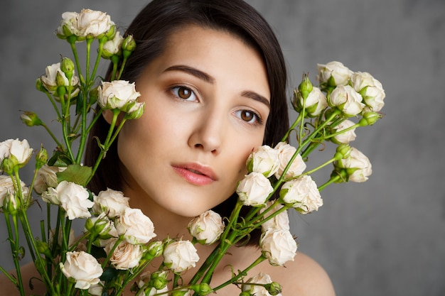 Zamyka w górę portreta czuła młoda kobieta z kwiatami nad szarości ścianą