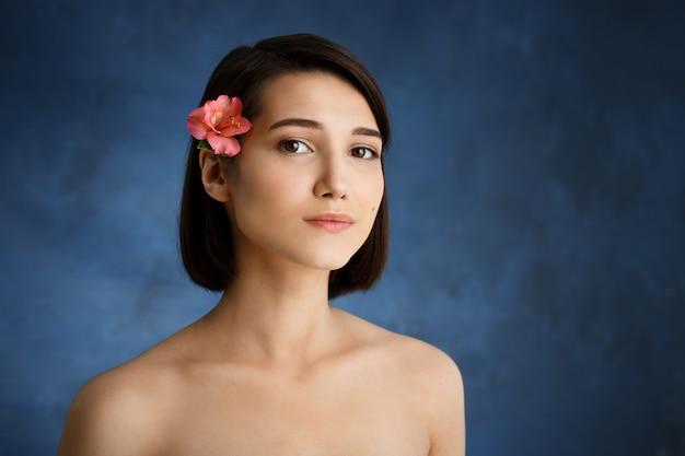 Zamyka w górę portreta czuła młoda kobieta z menchiami kwitnie w włosy nad błękit ścianą