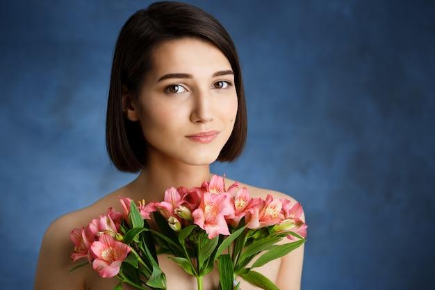 Zamyka w górę portreta czuła młoda kobieta z różowymi kwiatami nad błękit ścianą