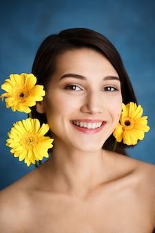 Zamyka w górę portreta czuła młoda kobieta z żółtymi kwiatami nad błękit ścianą