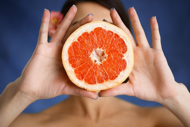 Zamyka w górę portreta czułego młodej kobiety mienia rżnięta pomarańcze nad błękit ścianą