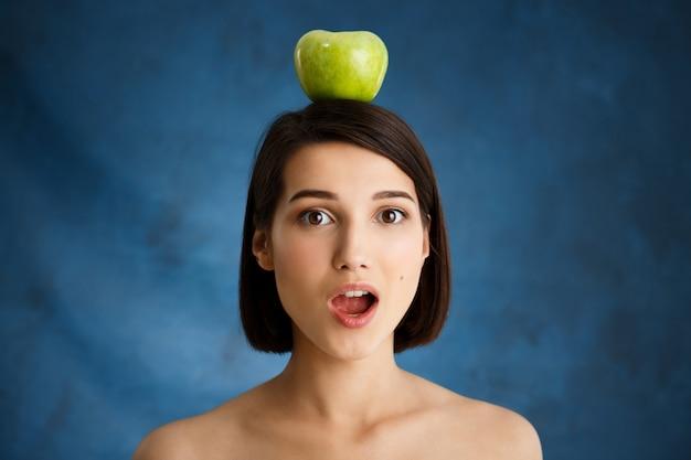 Zamyka w górę portreta czuły młodej kobiety mienia jabłko na jej głowie nad błękit ścianą