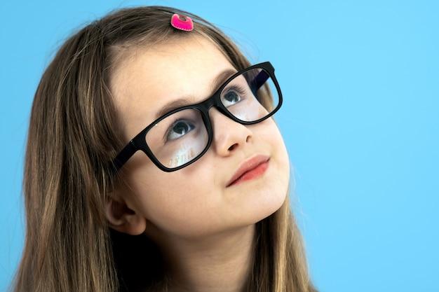 Zamyka w górę portreta dziecko szkolna dziewczyna jest ubranym przyglądających szkła odizolowywających na błękitnym tle.