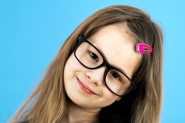 Zamyka w górę portreta dziecko szkolna dziewczyna jest ubranym przyglądających szkła