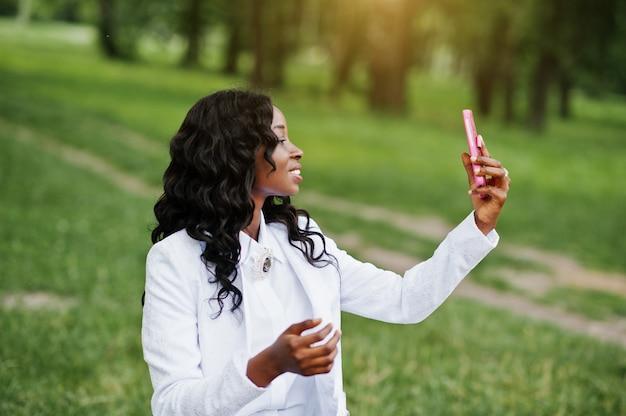 Zamyka w górę portreta elegancka czarnego amerykanina afrykańskiego pochodzenia dziewczyna bierze selfie z różowym telefonem komórkowym