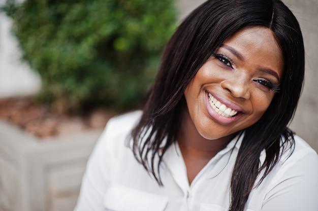 Zamyka w górę portreta formalnie ubierająca amerykanin afrykańskiego pochodzenia biznesowa kobieta w białej bluzce. udany bizneswoman ciemnoskórych.