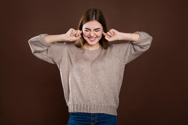 Zamyka w górę portreta gniewna zestresowana młoda kobieta czopuje ucho palcami, drażniąca głośnym irytującym hałasem, ma ból głowy lub migrenę. negatywne ludzkie emocje