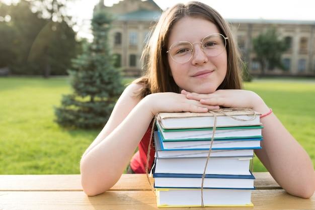 Zamyka w górę portreta highschool dziewczyny odpoczynkowa głowa na książkach