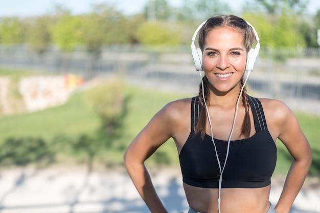 Zamyka w górę portreta kobieta robi sportowi odpoczywać plenerową uśmiechniętą i słuchającą muzykę