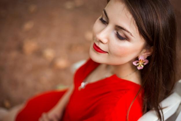 Zamyka w górę portreta kobieta w czerwieni sukni obsiadaniu na ławce w parku i marzyć coś. atrakcyjna młoda dziewczyna ma odpoczynek w parku