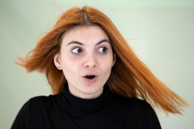 Zamyka w górę portreta ładna rudzielec dziewczyna z długim falistym włosy dmuchaniem na wiatrze.