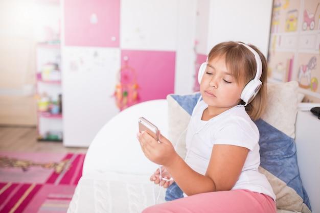 Zamyka w górę portreta mała caucasian urocza dziewczyna słucha muzyka w słuchawkach w wygodnej sypialni uśmiechniętej i relaksującej.