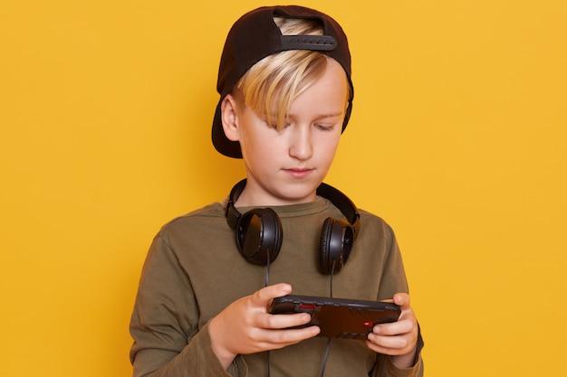 Zamyka w górę portreta mały blond chłopiec jest ubranym zieloną koszula