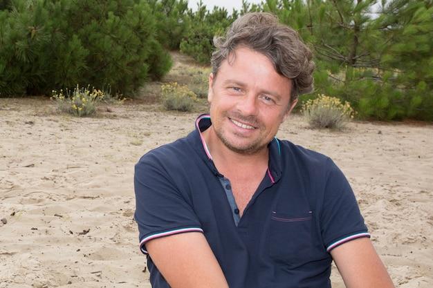 Zamyka w górę portreta mężczyzna trwanie outside w piasek plaży krajobrazie