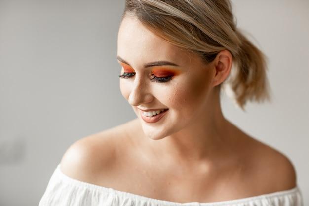 Zamyka w górę portreta młoda blond kobieta z kucykiem i pomarańczowobrązowym jaskrawym makeup na prostym tle. miejsce na tekst