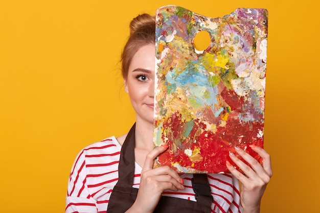 Zamyka w górę portreta młoda kobieta malarz przeciw kolor żółty ścianie, rysuje obrazek, dama jest ubranym przypadkową pasiastą koszula i brown fartucha