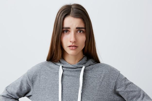 Zamyka w górę portreta młoda ładna nieszczęśliwa caucasian dziewczyna z ciemnymi długie włosy w przypadkowym szarym bluza z kapturem płacze, z mokrymi oczami po zerwania z chłopakiem. negatywne emocje