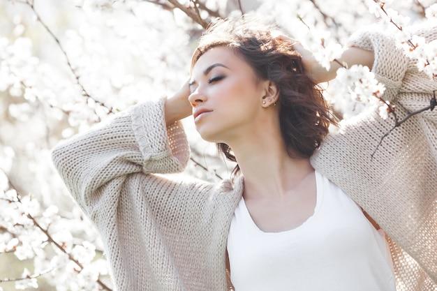 Zamyka w górę portreta młoda piękna kobieta na wiośnie. atrakcyjna młoda dziewczyna z kwiatami. model wiosennego makijażu.
