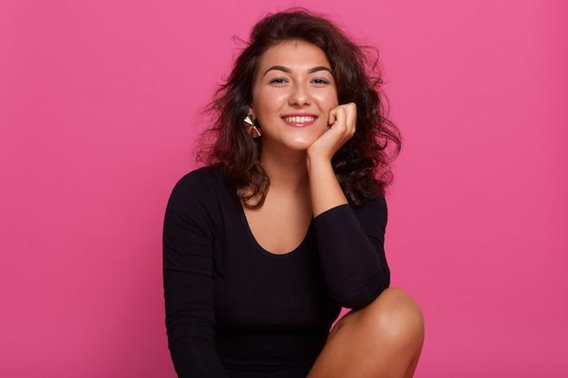 Zamyka w górę portreta młoda rozochocona piękna dziewczyna z ciemnym falistym włosy ubierał czarną koszula, siedzący ono uśmiecha się z zębami przeciw menchii ścianie